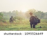 Soldier in the outoor during the military operation turning to combat helicopter approaching covering his eyes. Backup is coming,copy space.