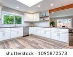 Stock photo open concept kitchen with white cabinets grey quartz countertops and tile backsplash 1095872573