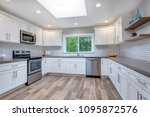 Stock photo open concept kitchen with white cabinets grey quartz countertops and tile backsplash 1095872576