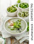 Small photo of Broad bean soup with fresh mint and feta cheese in a white bowl on a wooden table. Healthy and delicious vegetarian food
