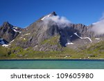 Picturesque mountain peaks towering above fjord on Lofoten islands in Norway - stock photo