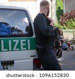 Small photo of Berlin, Germany - May 19, 2018: Back turned German policeman (Polizei) at work during the Carnival of Cultures (Karneval der Kulturen), multicultural festival in Kreuzberg, Berlin