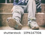 Stock photo old broken shoes of a little boy as a symbol for child poverty 1096167506