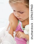 Worried little girl getting an injection or vaccine - looking at the needle - stock photo
