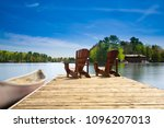 two muskoka chairs sitting on a ... | Shutterstock . vector #1096207013