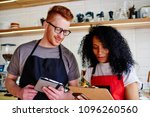 Stock photo positive male waiter and female waitress checking offering standing in coffee shop young man and 1096260560