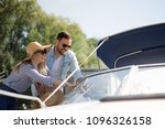 Small photo of A beautiful young couple watches a motor boat that they intend to buy.