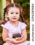Pretty baby girl holding in his hand young hedgehog outdoors closeup