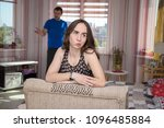 Small photo of family conflict. Family conflict and the difficulties of the father and daughter in her room. The daughter sits right in front of the camera and looks unhappy