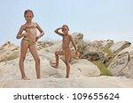 Girls on the rocky beach - stock photo