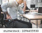Small photo of Unhappy weary employer feeling pain in back. He keeping it by hand while sitting at table during labor. Worker with bad state of health concept