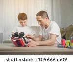 cheerful father is repairing... | Shutterstock . vector #1096665509