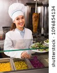 Small photo of Young female cook offering salad at bistro counter and smiling