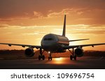 Airplane at sunset - back lit - stock photo