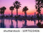 Small photo of Duress, Albania. May 2018: People photographing scenic sunset in local resort with pool and palm trees.