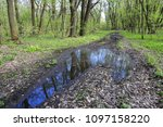 puddle on dirt road in spring... | Shutterstock . vector #1097158220