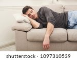 young casual man sleeping on... | Shutterstock . vector #1097310539