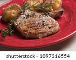 Small photo of Spicy pork loin chop steak served over roasted potato