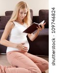 Young pregnant blonde woman sitting on the floor and reading book - stock photo