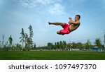 Small photo of Tricking on lawn in park. Man makes kick in jump with turn. Martial arts.