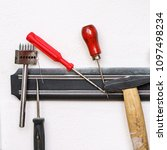 Small photo of Set of tanner tools close-up. Awl, screwdrivers and hammer hang on the magnetic holder.