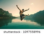 man jumping with joy by a lake | Shutterstock . vector #1097558996