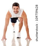 Competitive male athlete ready to run - isolated over a white background - stock photo