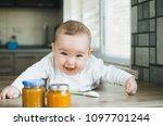 Small photo of baby with blue eyes wants to try fruit puree while lying on the table on his stomach