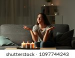 Small photo of Woman complaining during a blackout sitting on a couch in the living room at home