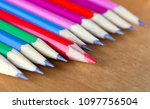 Small photo of black lead pencils lie in a row, one pencil has a red core and put forward, small depth of sharpness