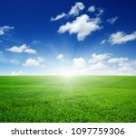 green field  blue sky and sun.  | Shutterstock . vector #1097759306