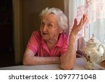elderly woman sits at the... | Shutterstock . vector #1097771048