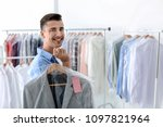 young man holding hanger with... | Shutterstock . vector #1097821964