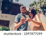 couple using their phone while... | Shutterstock . vector #1097877299