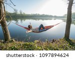 young man by the lake hanging... | Shutterstock . vector #1097894624