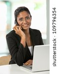 Portrait of an Indian business woman using cell phone. - stock photo