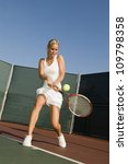 A Female Tennis Player Hitting...