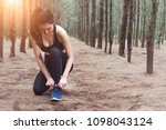 woman tying up shoelaces when... | Shutterstock . vector #1098043124