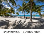 Small photo of Marathon, Florida / USA - 06/20/2017: Beach scene with sand, palm trees, and palm tree shadows. Post card like yet very bold and colorful, Very well framed for composition