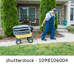 man pulling a heavy wheelbarrow ... | Shutterstock . vector #1098106004