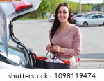 young woman puts bags from the... | Shutterstock . vector #1098119474