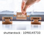 Small photo of Hand holding a wooden puzzle with the word solution. There is a matching puzzle next to it with the word problem. The concept of solving problems, all problems can be solved.