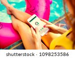 girl playing on a phone poolside | Shutterstock . vector #1098253586