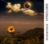 Small photo of Scientific natural phenomenon. The Moon covering the Sun. Total solar eclipse with diamond ring effect above mountain range and sunflower. Beautiful nature and serenity landscape.