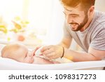 father bathes baby in baby bath ... | Shutterstock . vector #1098317273