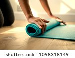 woman rolling up a yoga mat | Shutterstock . vector #1098318149