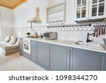 Stock photo wide angle shot of modern open living room with grey kitchen counters and white furniture in 1098344270