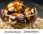 Profiteroles with chocolate sauce and chocolate syrup in a glass bowl. Close up - stock photo