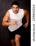 Sportive man running and looking very competitive - stock photo