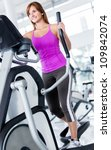 Woman exercising at the gym on a cross trainer - stock photo